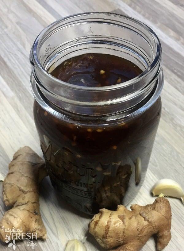 Homemade Teriyaki Sauce in a mason jar with ginger root and garlic at the base