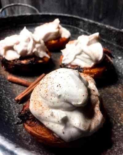 Grilled peaches, topped with coconute whipped cream on a glavinized tray with cinnamon sticks for garnish.