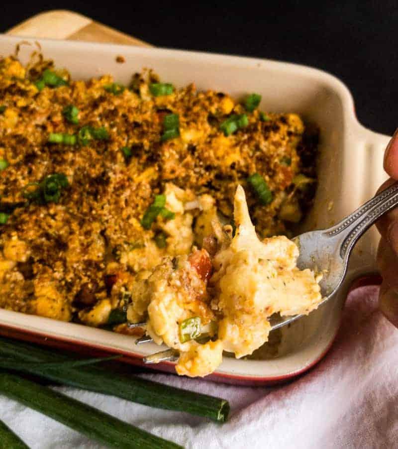 A bite of Cheesy Cauliflower Casserole held above the casserole dish.
