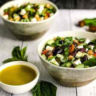 Close up of Mediterranean Chickpea Salad in a faux wood bowl with a second bowl blurred in the background.
