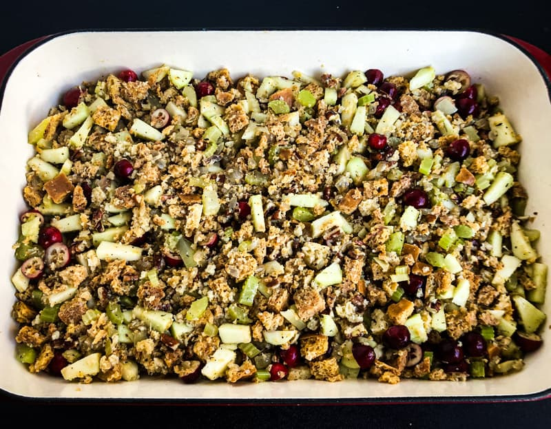 Stuffing ingredients mixed together in a casserole dish ready to go in the oven.