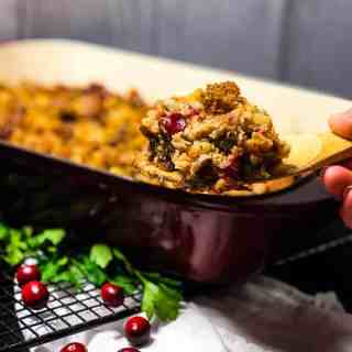 A serving of Gluten-free Vegetarian Stuffing on a wooden spatula with casserole in the background.