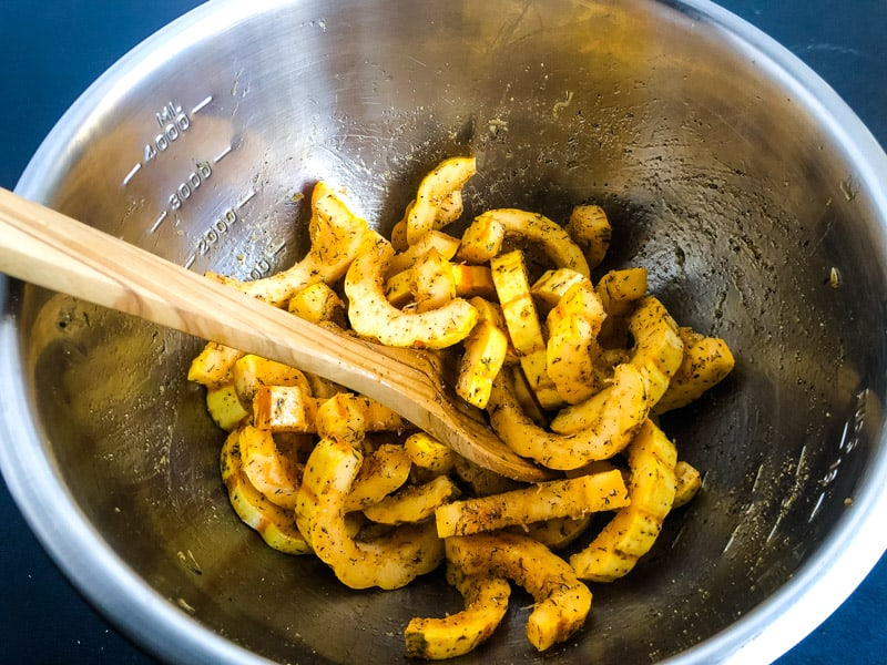 Tossing delicata squash with olive oil and seasoning in a stainless steel bowl