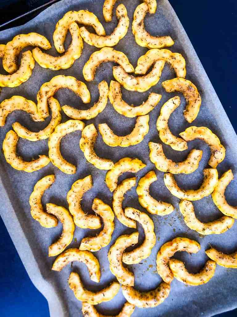 Delicata Squash ready to roast on a sheet pan lined with parchment paper