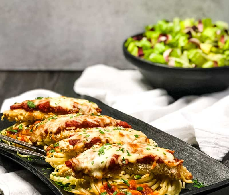 Side view of Air Fryer Chicken Parmesan on top of linguine on a black serving platter with a salad in the background.