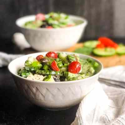 Greek Inspired Cucumber Salad in a white bowl with a second bowl and cucumbers and tomatoes blurred in the background.