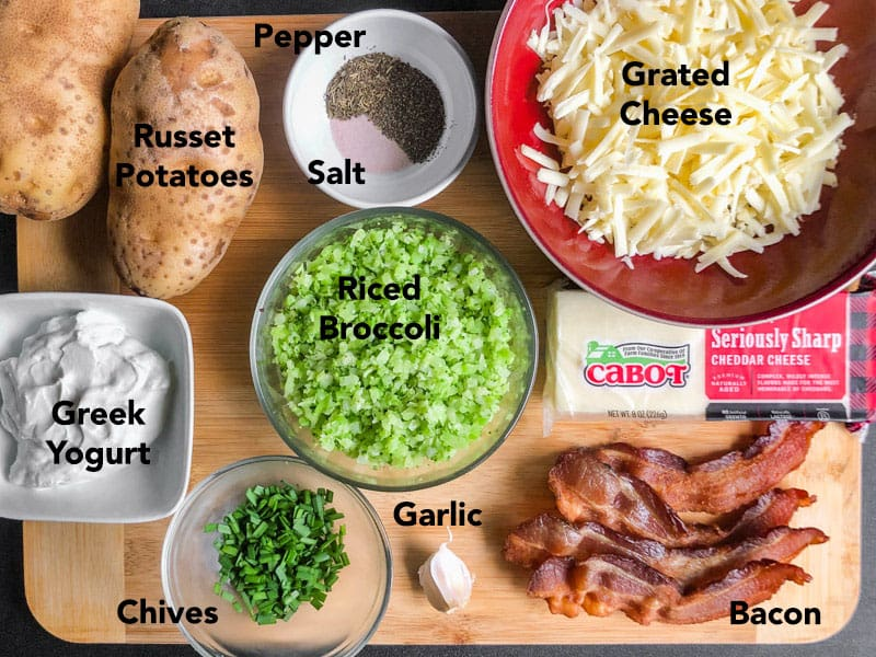 Prepped ingredients on a wood cutting board: russet potatoes, shredded cheese, bacon, riced broccoli, chives, Greek yogurt, garlic, and salt and pepper.