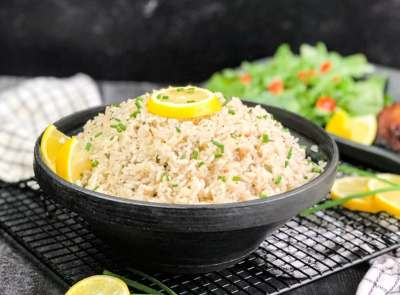 Coconut Rice in a black bowl garnished with lemon and chives with a blurred salad in the background.