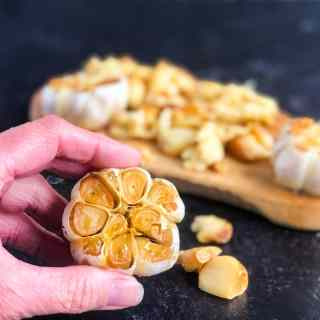 Close up of a hand holding a head of roasted garlic over a cutting board.