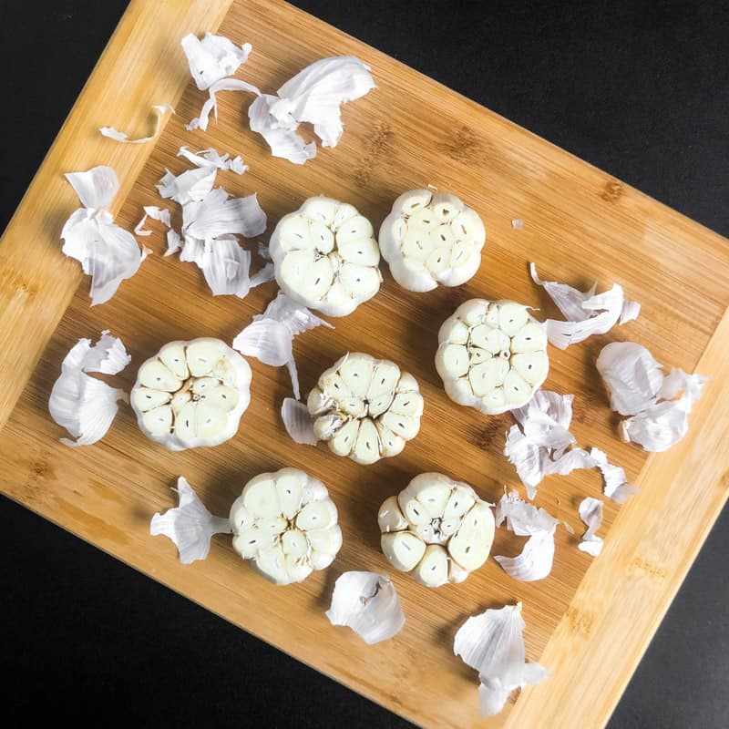 Heads of garlic with the tops cut off and loose papery peel removed on a wood cutting board.