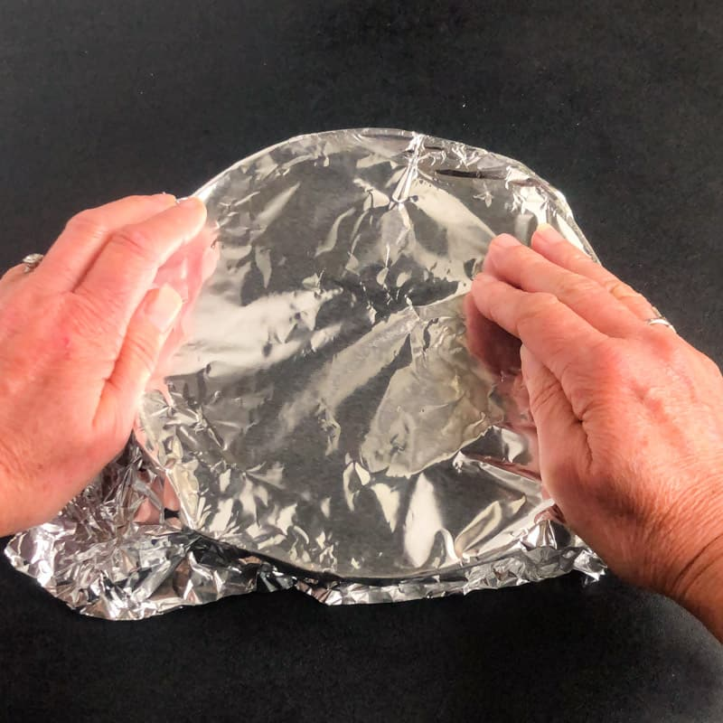Hands covering the skillet with aluminum foil.