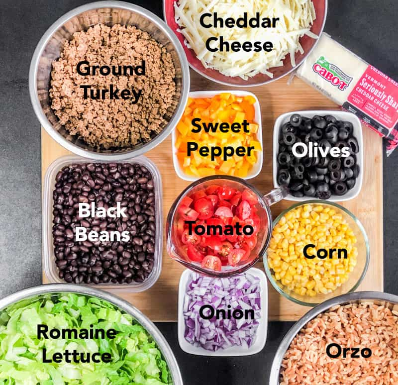 Prepped ingredients for Taco Pasta Salad on a wood cutting board including: seasoned ground turkey, shredded Cabot cheddar cheese, black beans, orzo, corn, red onion, chopped tomatoes, sweet peppers, romaine lettuce.