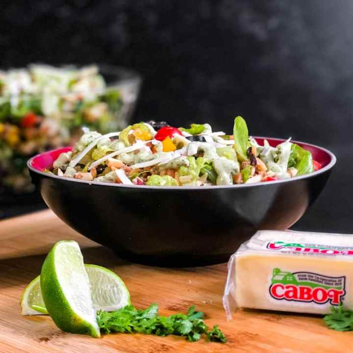 Side shot of Taco Pasta Salad on a wood cutting board with Cabot Cheese and sliced limes in the foreground and a large glass bowl of taco salad blurred in the background.