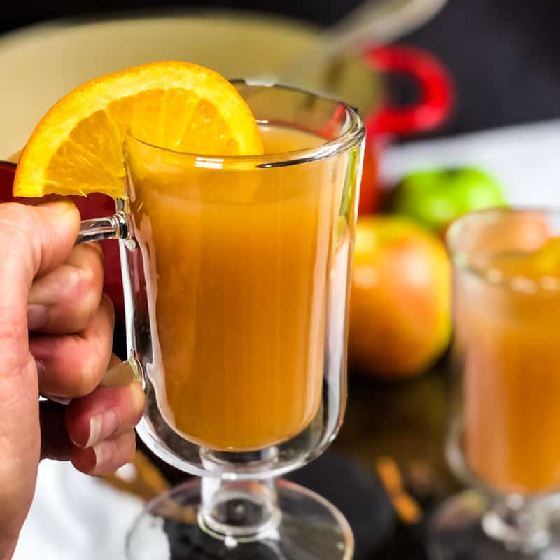 Hand holding a mug of spiced cider with Dutch oven and apples blurred in the background.
