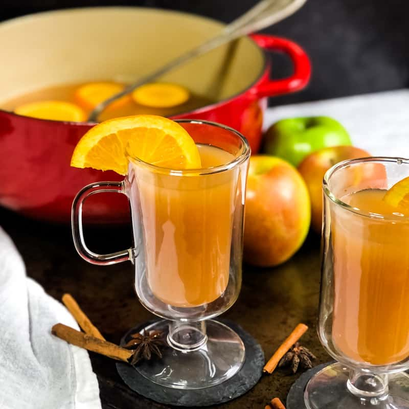 Two glass mugs of spiced cider garnished with orange slices.