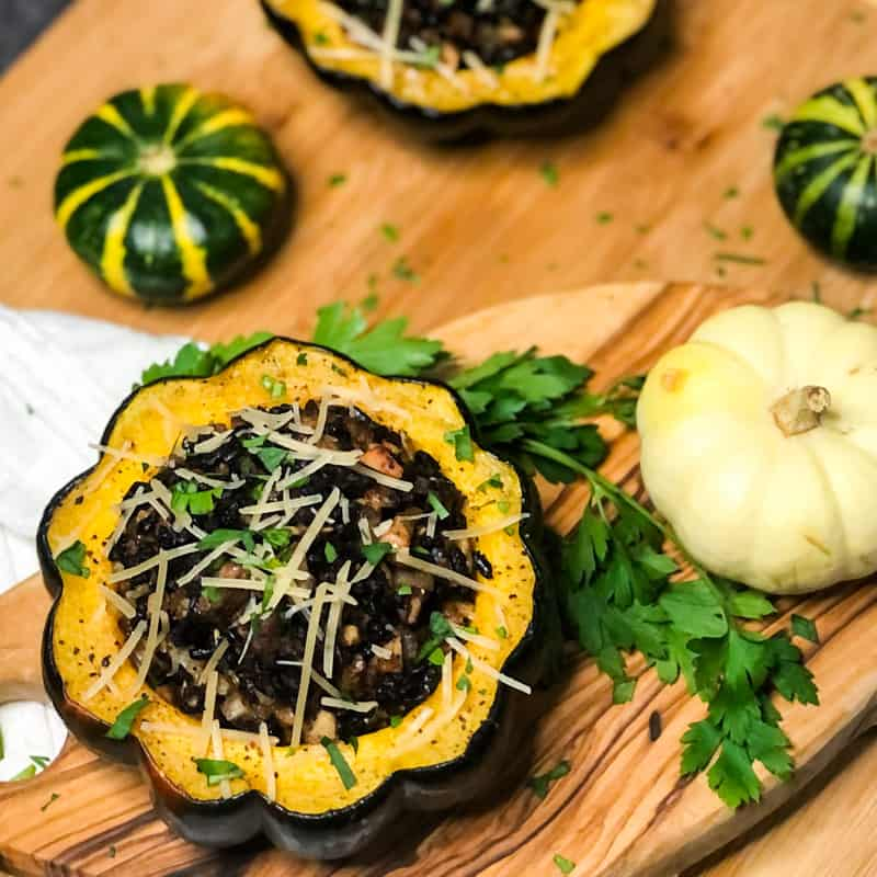 Overhead close up shot of Vegetarain Stuffed Acorn Squash on a wood cutting board garnished with parmesan cheese and parsley with mini pumpkins in background.