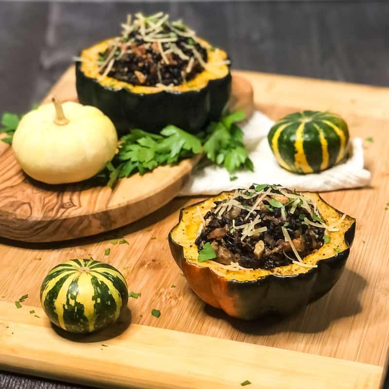 Tablescape shot of Vegetarian Stuffed Acorn Squash on wood cutting board with mini pumpkins blurred in background.