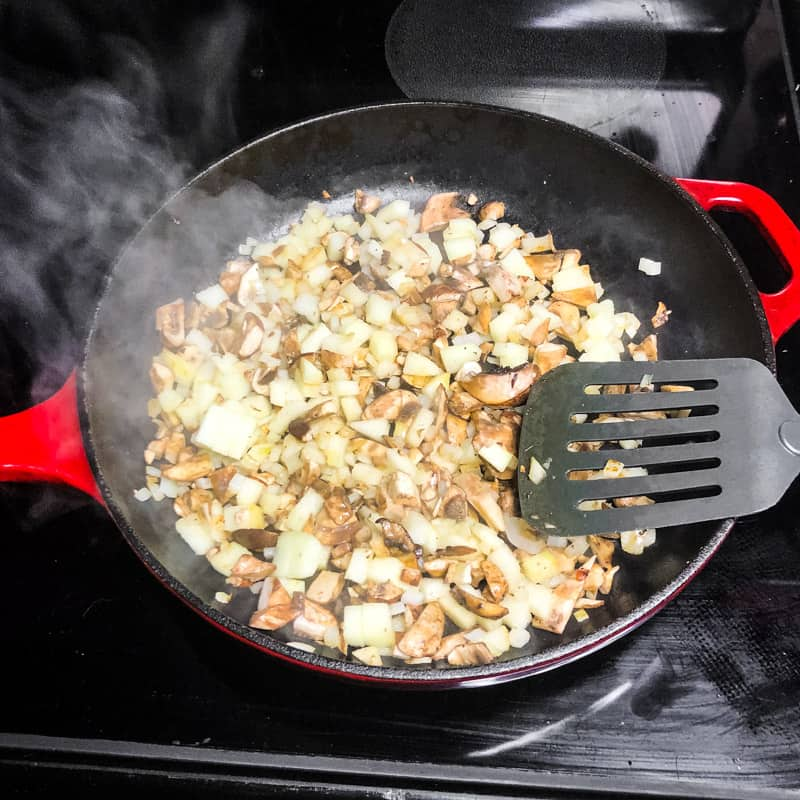 Mushrooms, onion, and apples cooking in a cast iron skillet on the stovetop.