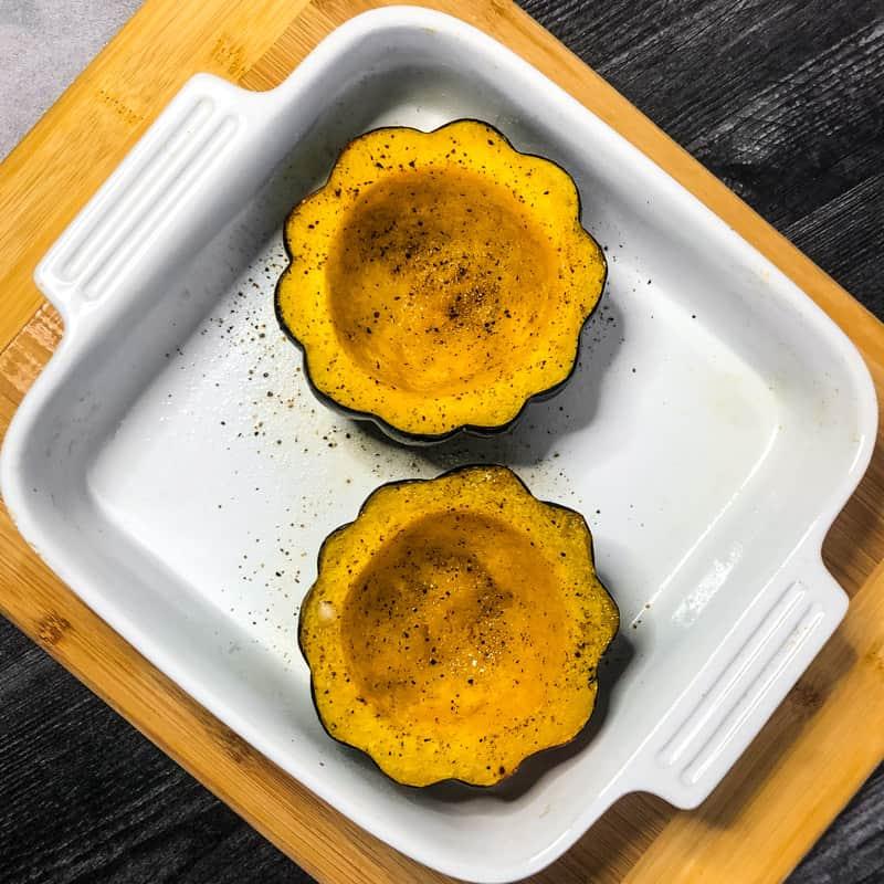 Roasted acorn squash halves in a white baking dish.