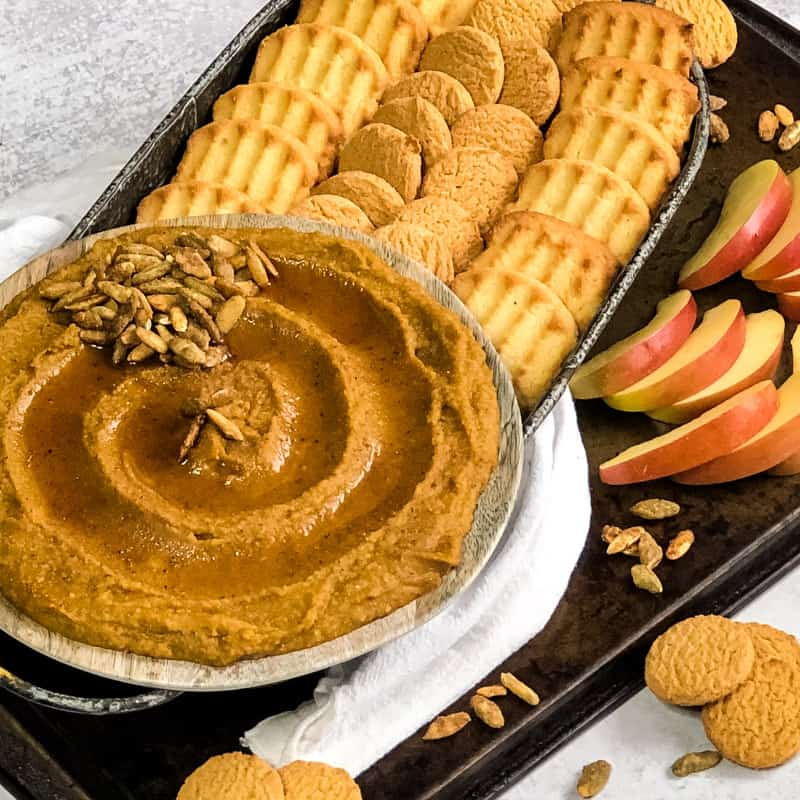 Pumpkin Pie Hummus swirled on a plate, drizzled with maple syrup, with rows of cookies and apples for dipping.