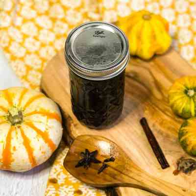 Overhead shot of jar of simple syrup on a wood platter with small pumpkins in background.