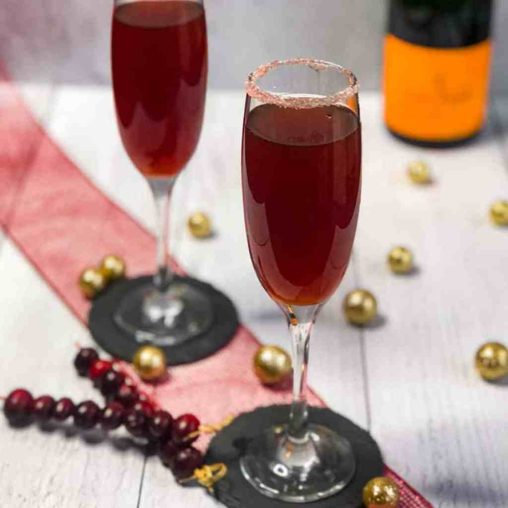 Cranberry Mimosas on a red ribbon with cranberries and gold balls below.