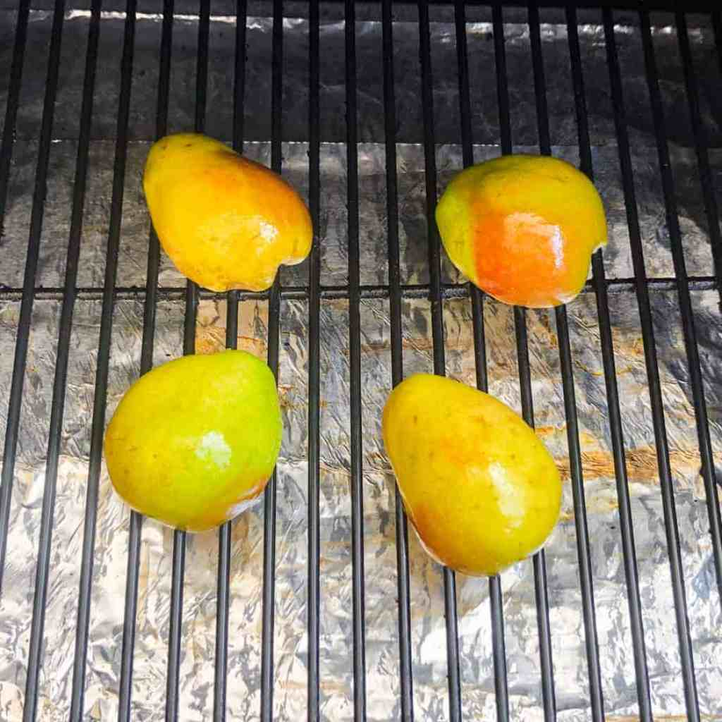 Halved pears on the grill cut side down.