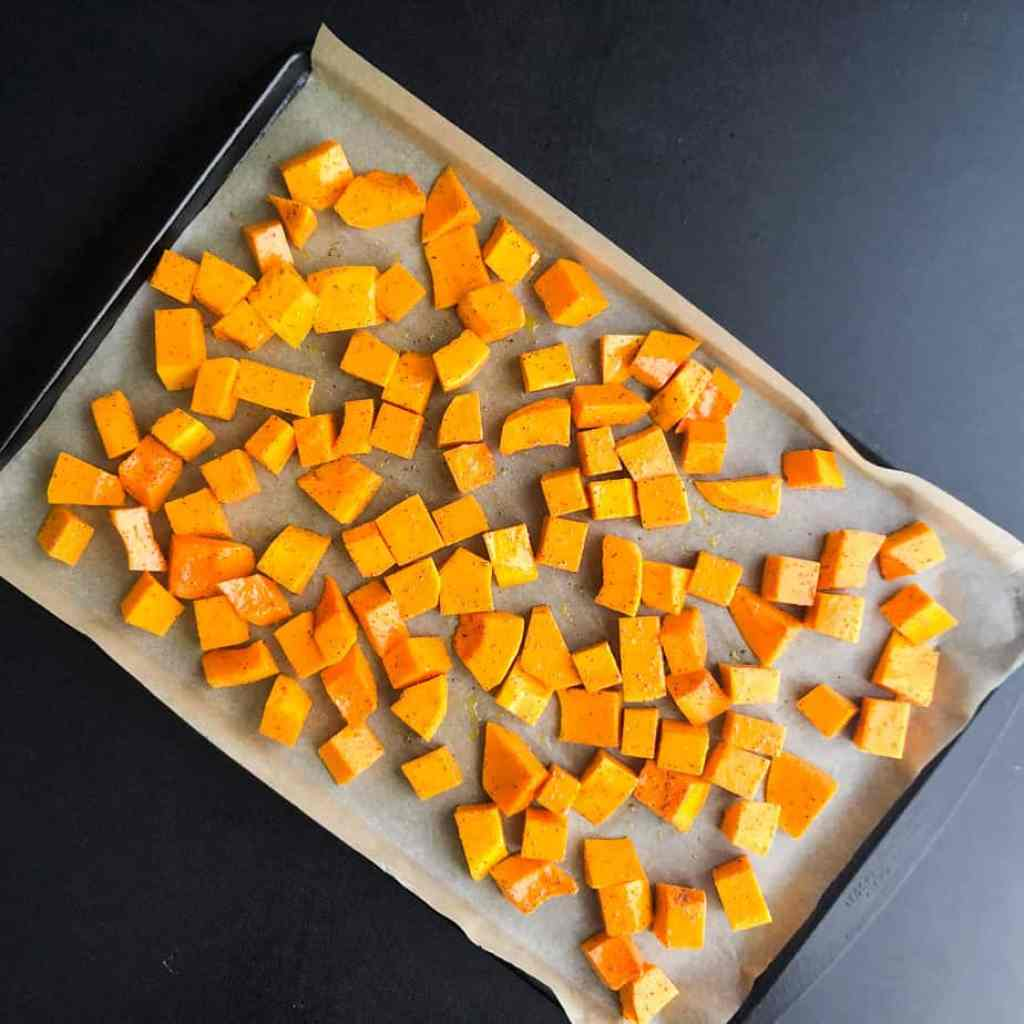 Butternut squash on a parchment lined baking sheet ready to go in the oven.