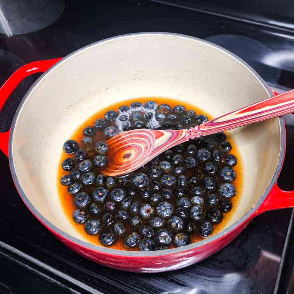 Blueberry sauce ingredients in a Dutch oven before the mixture comes to a boil.
