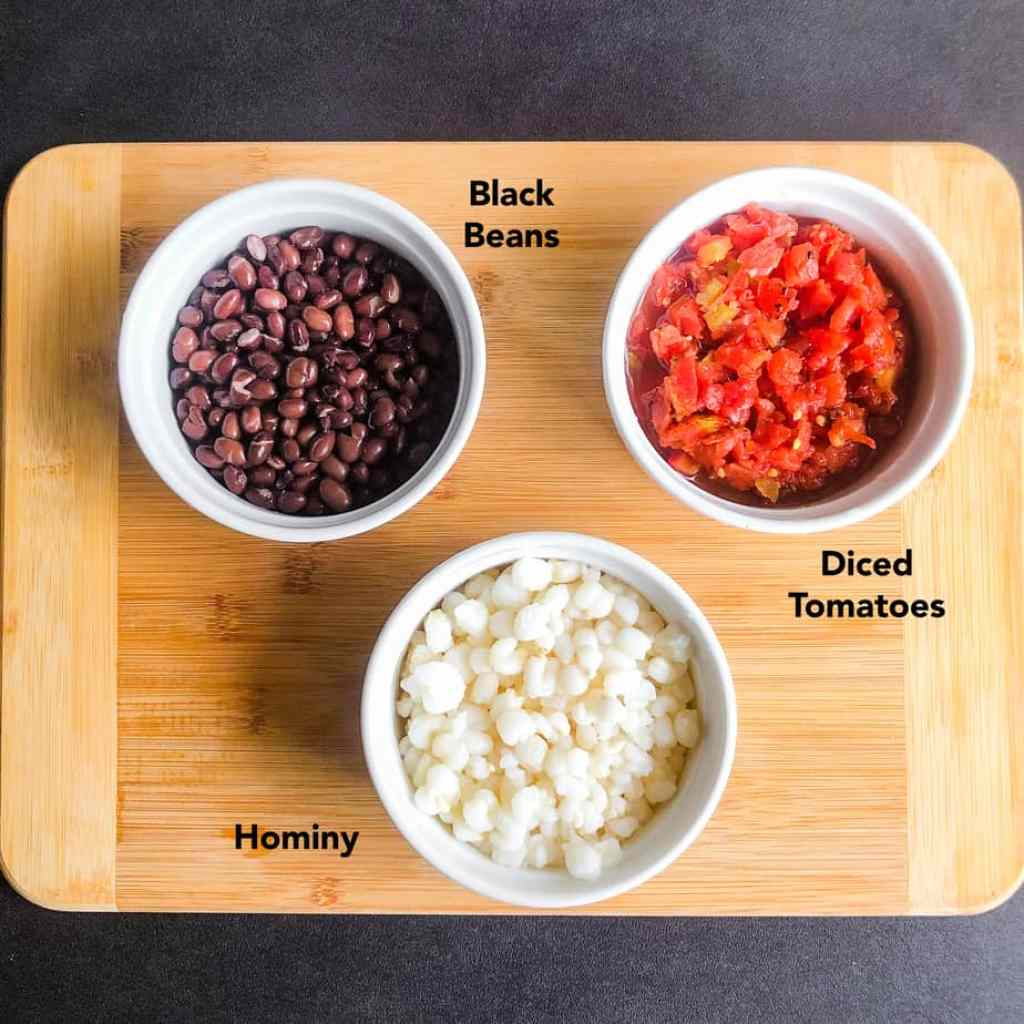 Bowls of black beans, hominy, and diced tomatoes on a wood cutting board.