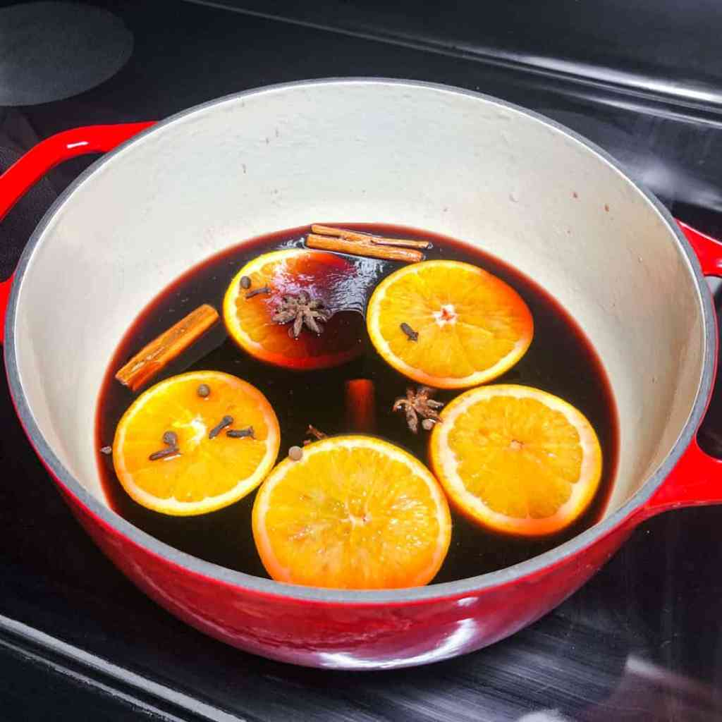 Wine, brandy, oranges, and spices added to Dutch oven to simmer on the stove.