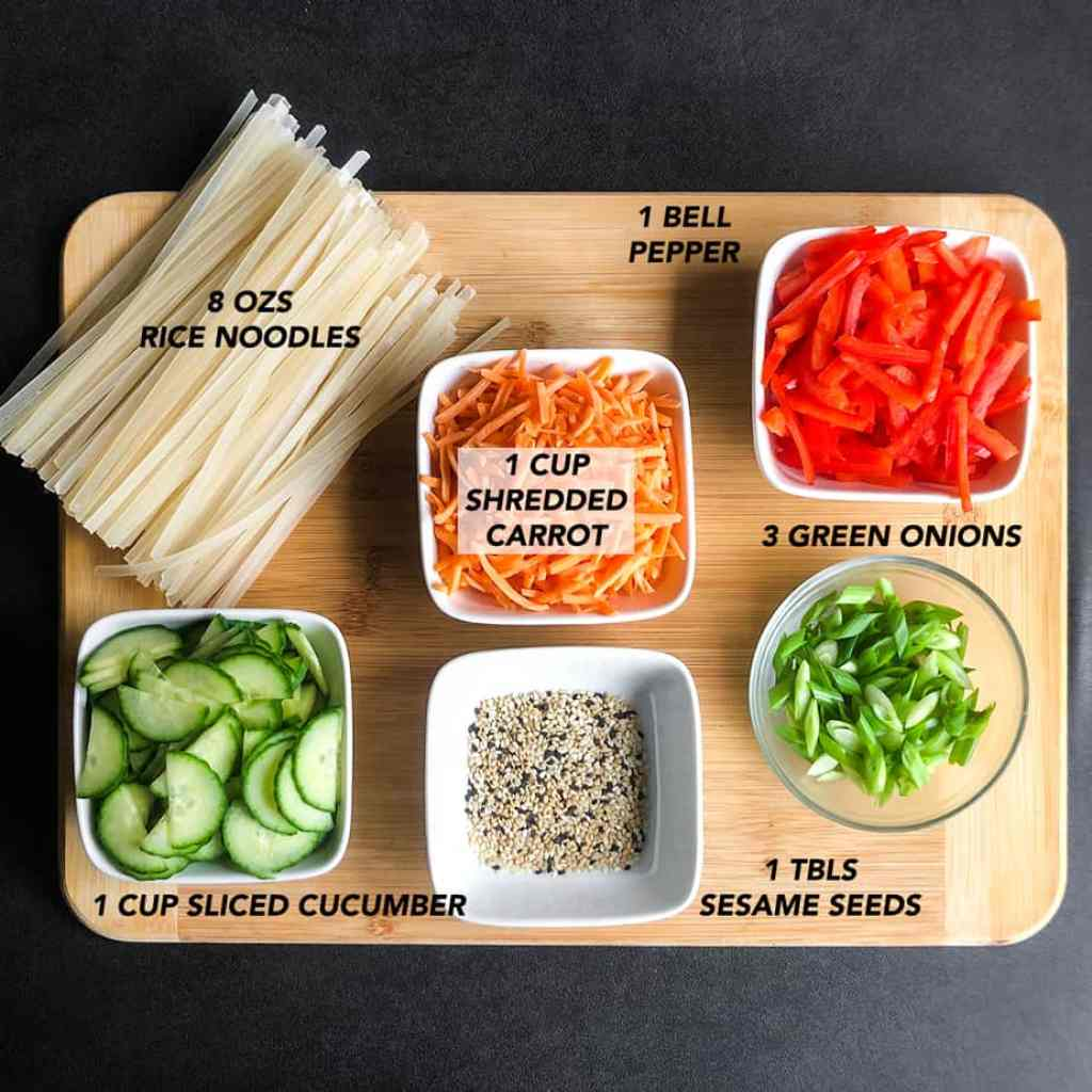 Salad ingredients cut and prepped on a wood cutting board.