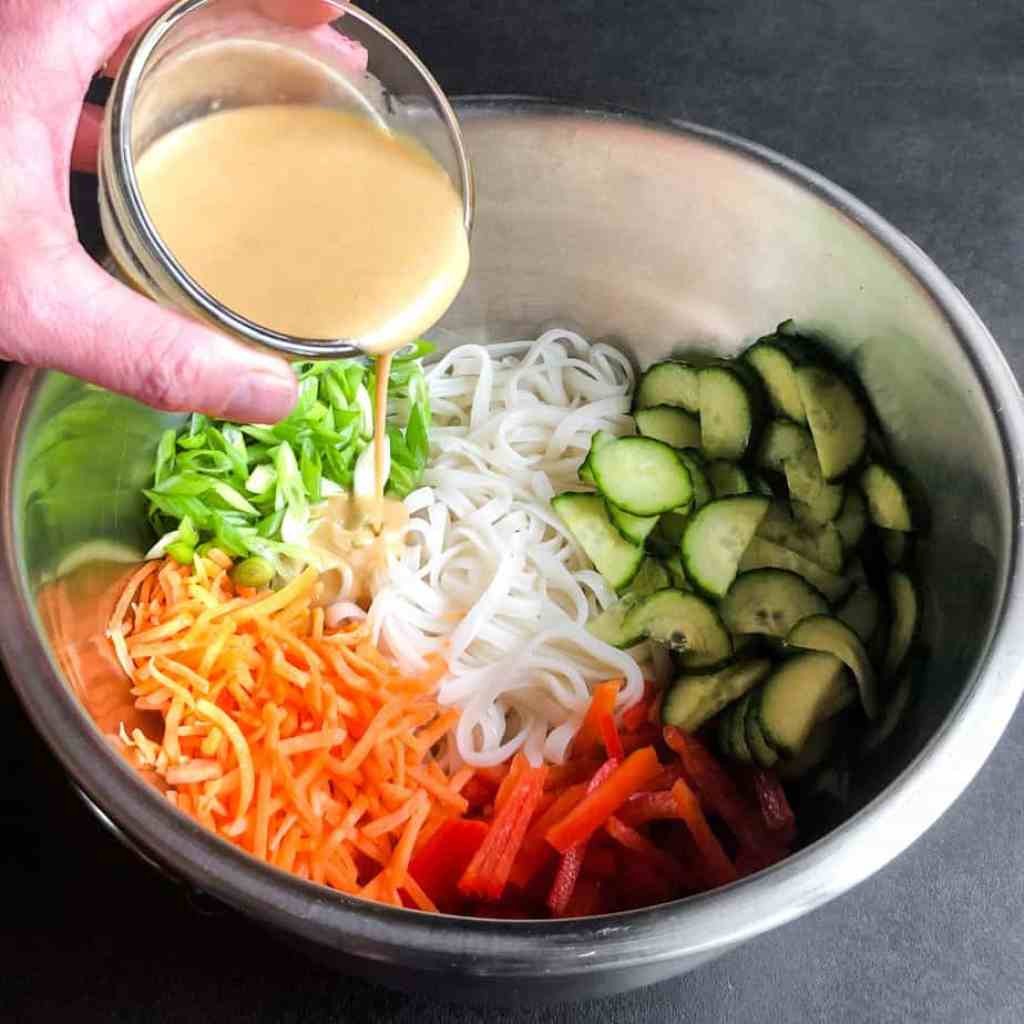 Hand pourning miso ginger dressing into a stainless steel bowl filled with salad ingredients.