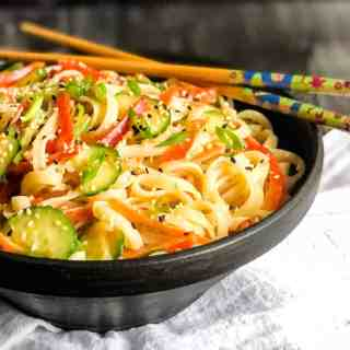 Close up of rice noodle salad in a black bowl.
