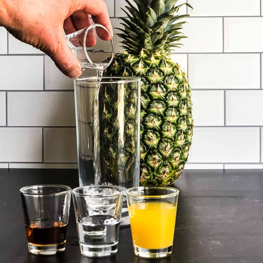 Hand pouring the silver rum into a glass with shot glasses of other ingredients in front.