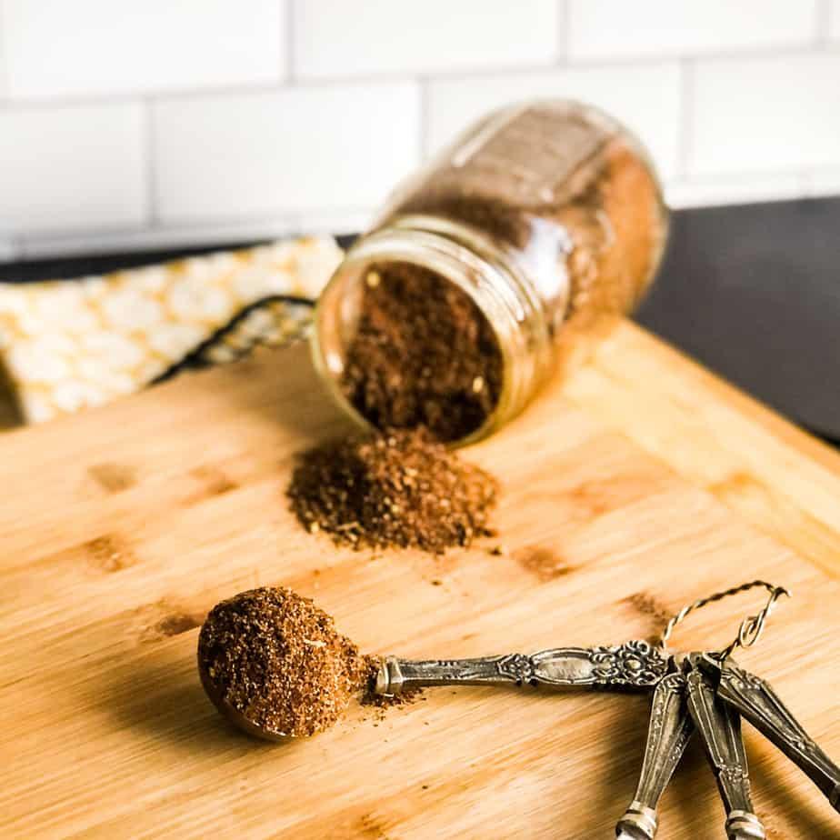 Overhead shot of taco seasoning on tablespoon on wood cutting board with jar of seasoning mix on it's side.