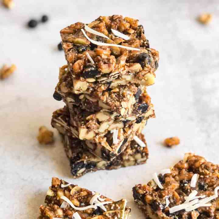Stack of walnut bars with dried bluberries and walnuts blurred in background.