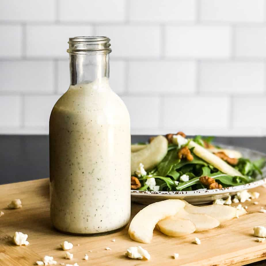 Gorgonzola Dressing in front of a plate of salad on a wood cutting board.
