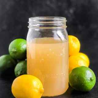 Homemade Sour Mix in a quart jar surrounded by lemons and limes.