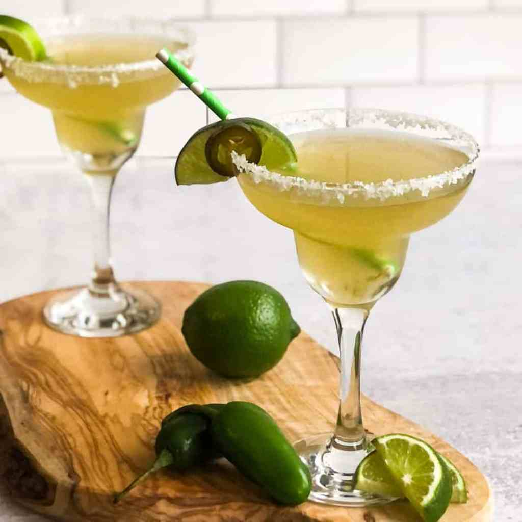 Two Jalapeno Margaritas on a wood cutting board garnished with a lime wedge and jalapeno slice.