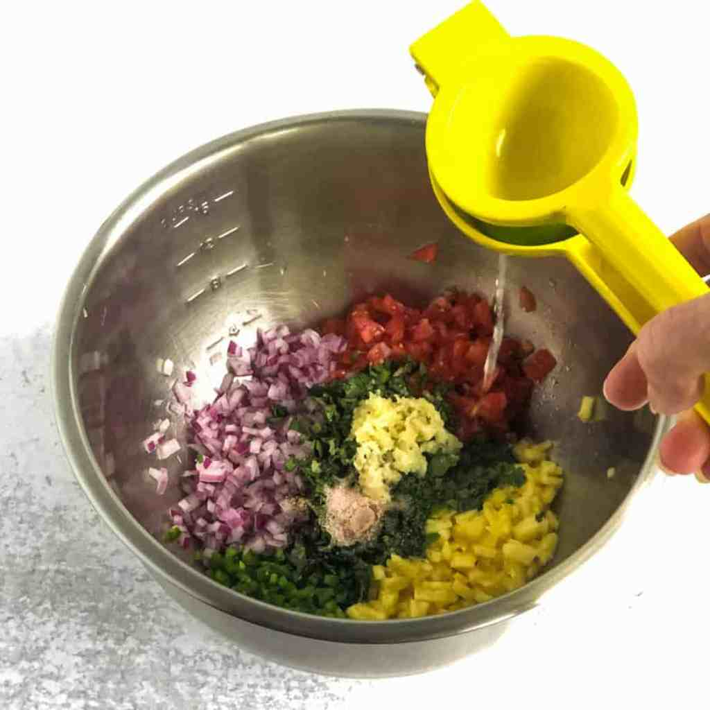 Hand holding a citrus juicer over a bowl of chopped pineapple, tomato, onion, jalapeno, and cilantro.