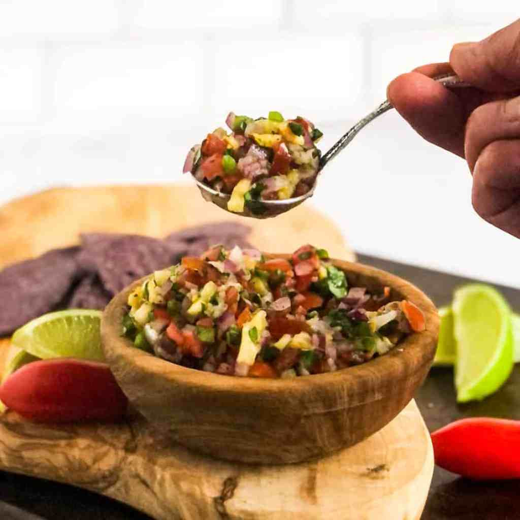 Hand holding a spoon of pico de gallo over a woden bowl of the salsa.