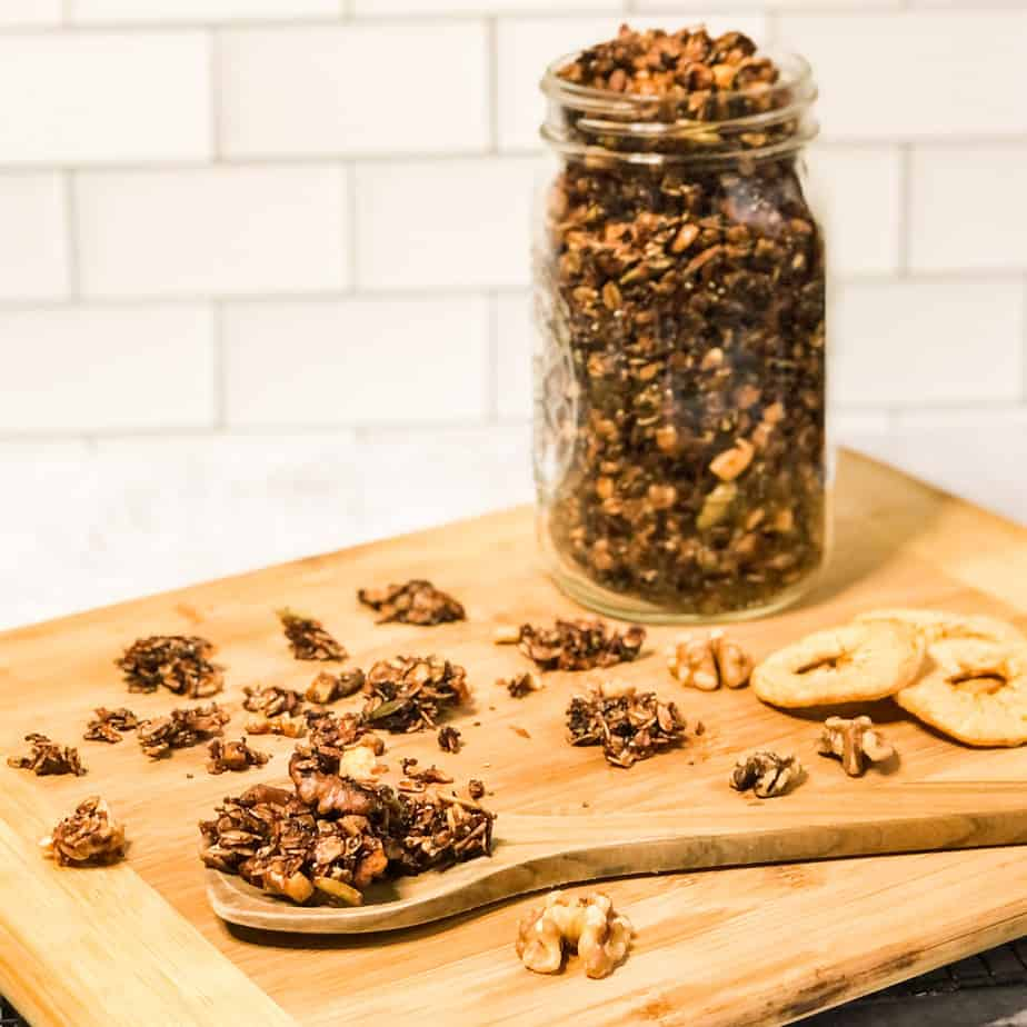 Spoon of granola on a wood cutting board garnished with granola clumps, walnuts, and dried apple rings.