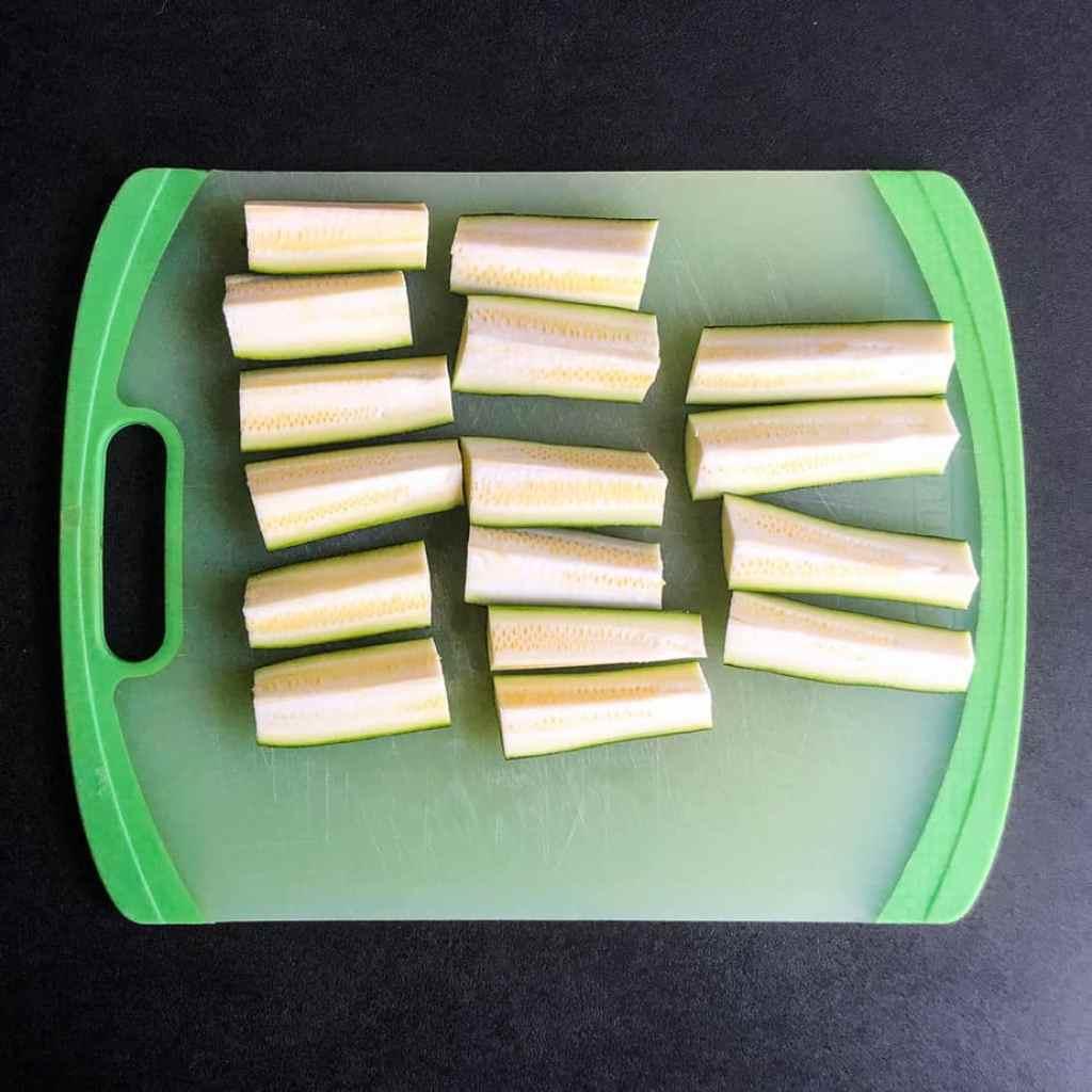 Zucchine wedges cut on green cutting board.