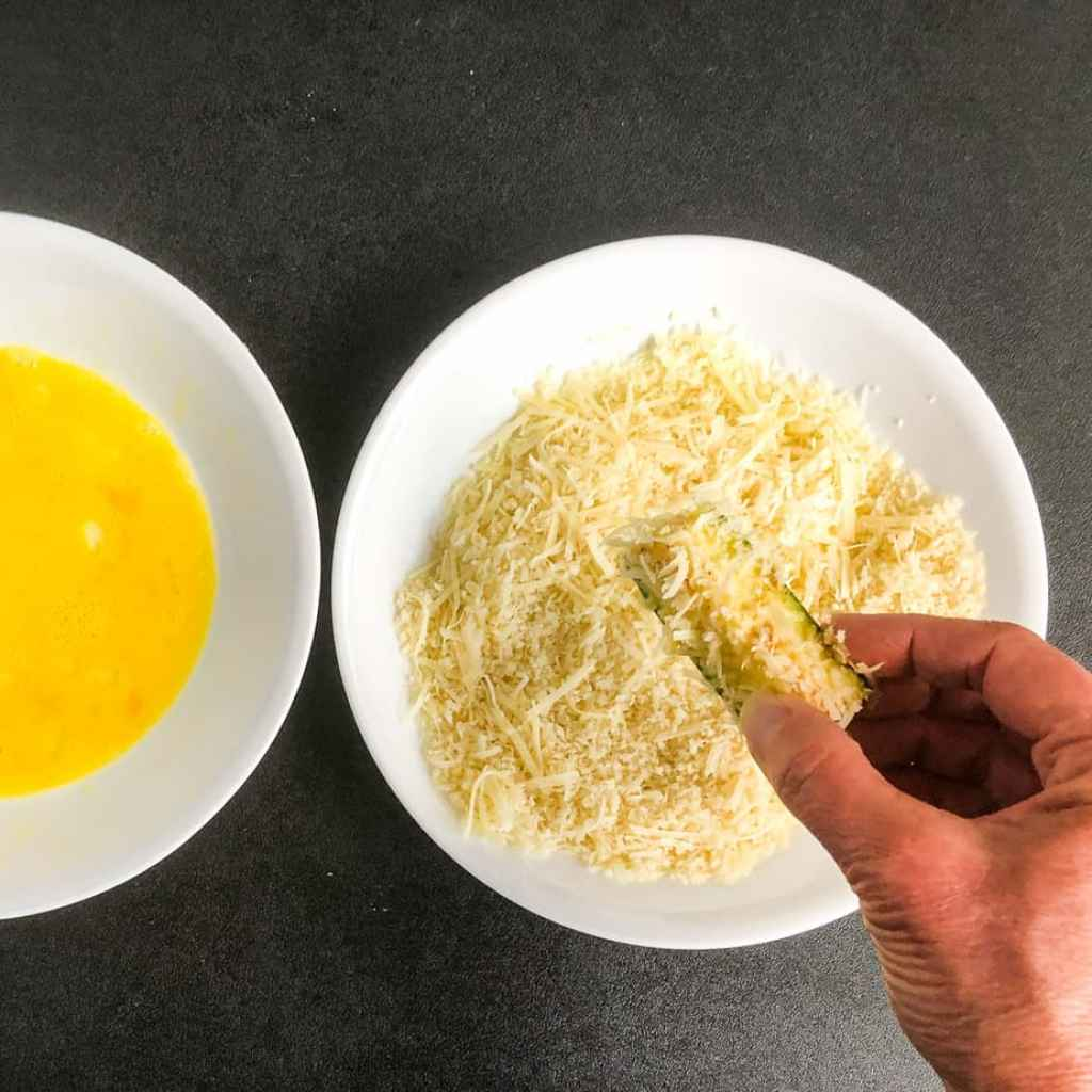 Hand dipping zucchini fry in parmesan and panko mixture.
