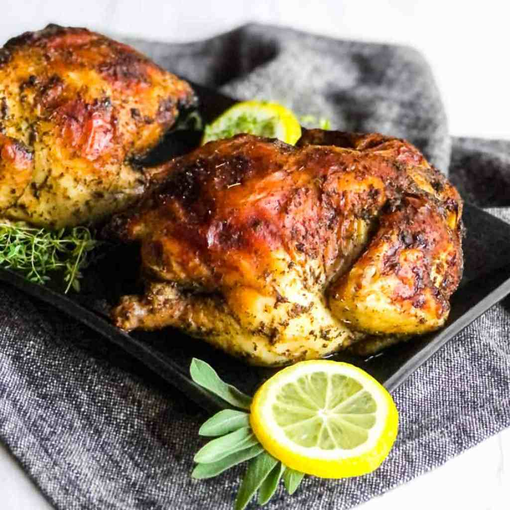 Two Cornish hens on a black platter garnished with lemon wheels, sage, and thyme.