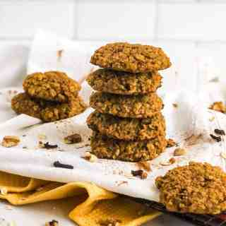 Stack of five Pumpkin Oatmeal Cookies on a white tea towel garnished with walnut pieces, whole cloves, and sprinkles of cinnamon.