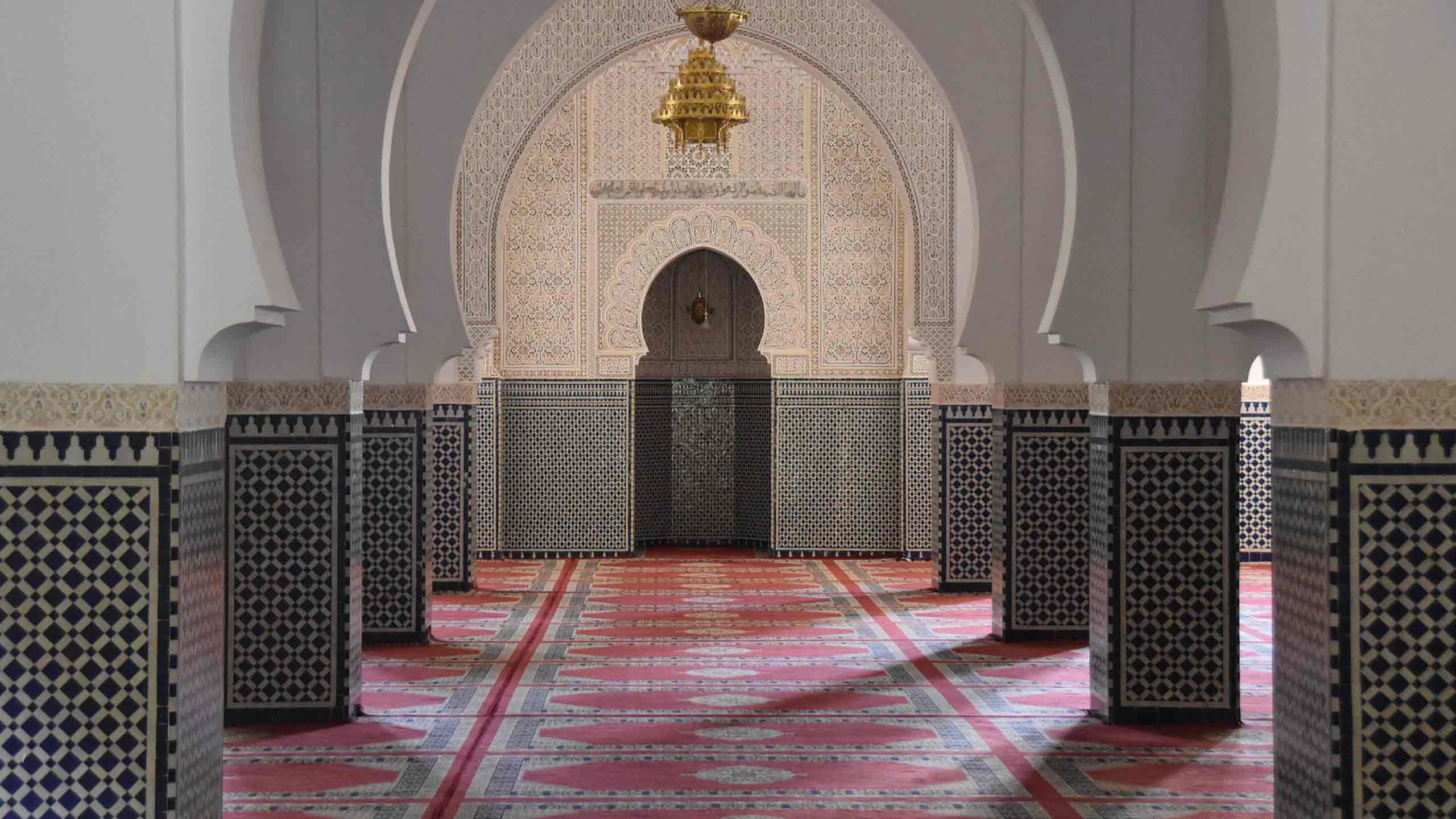 interior of mosque with mosaic on walls and carpet