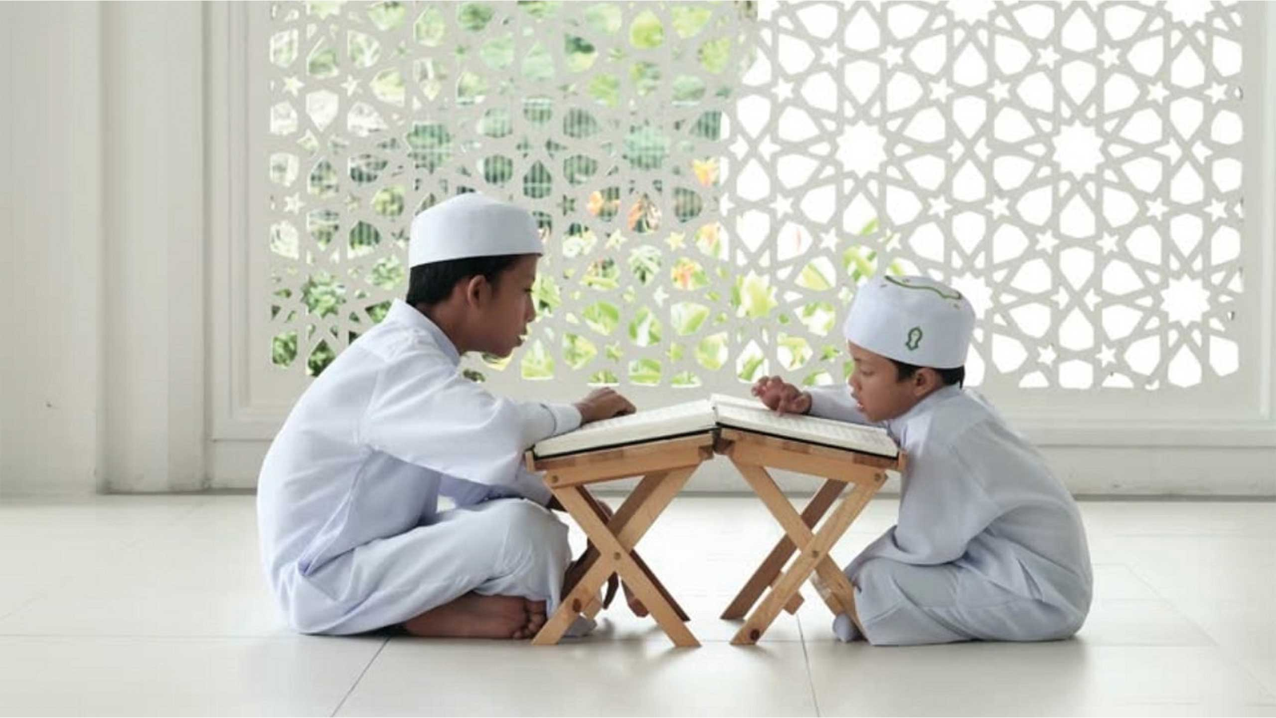 two children sitting reading quran