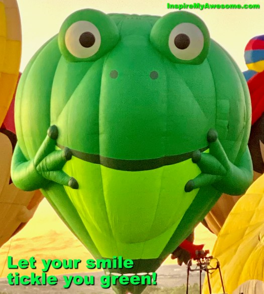 A hot air balloon in the shape of a frog, smiling. Let your smile tickle you green.